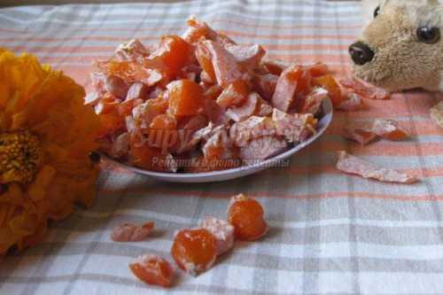 Вымоченные и очищенные от кожицы апельсиновые корочки нужно нарезать тонкими полосками, залить свежей водой и прокипятить в течение минут, а после дать хорошенько стечь, переложить в кастрюлю, засыпать сахаром и поставить на медленный огонь, периодически помешивая